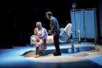"""Descargar fotografía con Willy Méndez sentado en una cama hospitalaria y Felipe Cotelo de pie en una escena del espectáculo """"Flechas del ángel del olvido""""."""